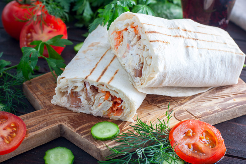 shaurma-with-chicken-cabbage-carrots-and-tomatoes-on-a-wooden-table-horizontal