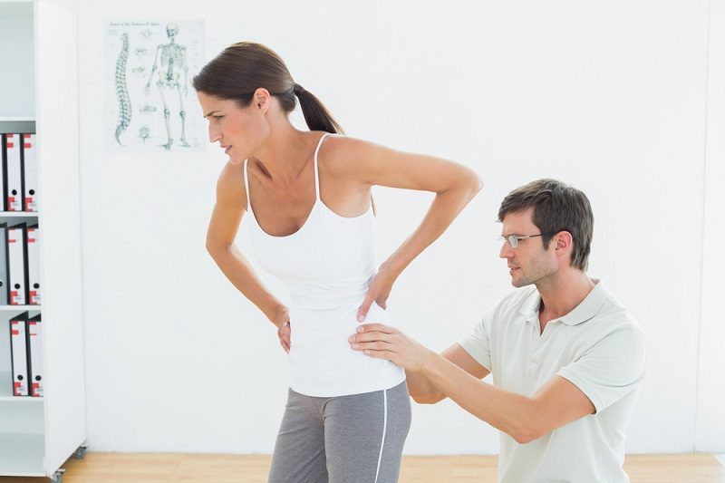 side-view-of-a-male-physiotherapist-examining-woman-s-back-in-the-medical-office-2