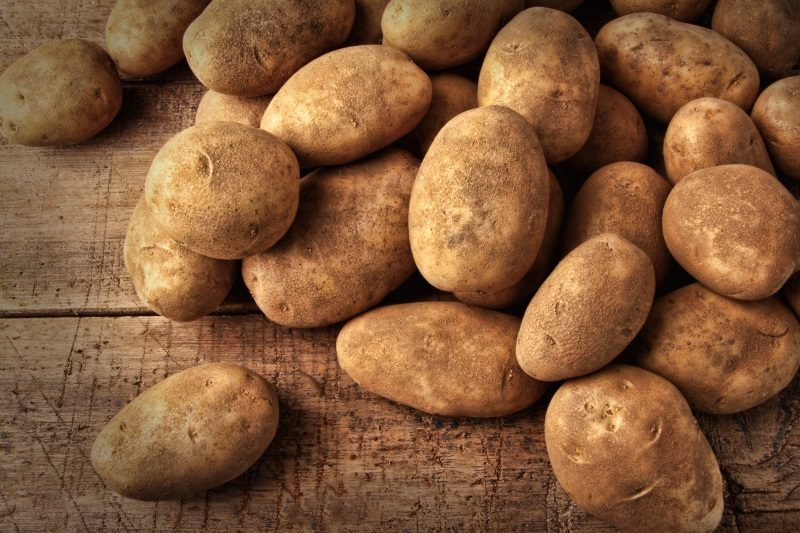 fresh-potatoes-on-rustic-wooden-background
