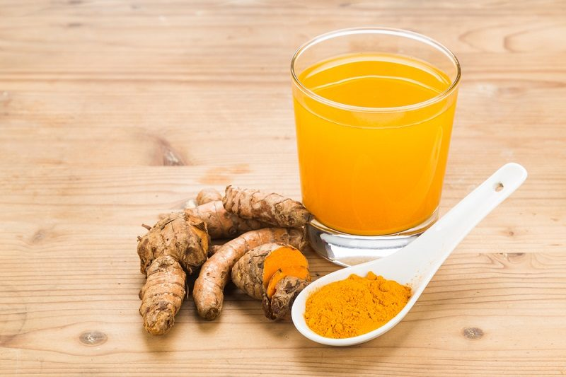 healthy-turmeric-roots-drinks-in-a-transparent-glass-on-wooden-s