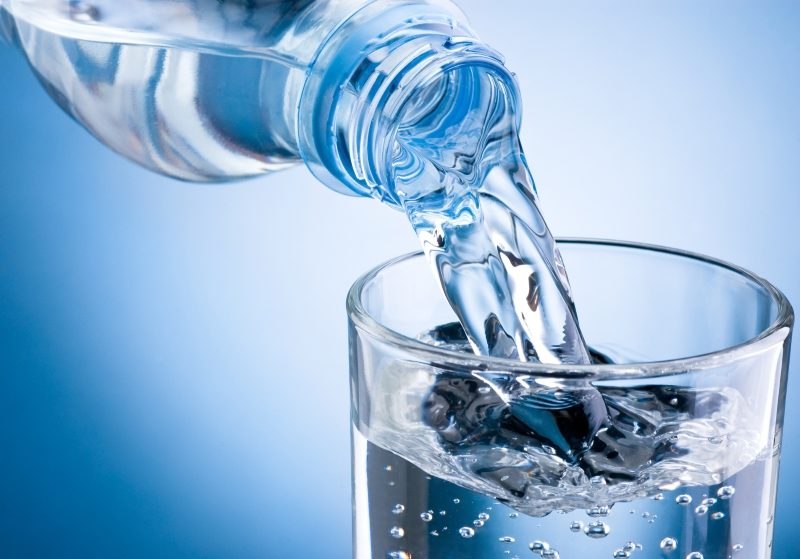 pouring-water-from-bottle-into-glass-on-blue-background-2