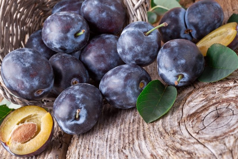 plums-with-leafs-on-wood-background