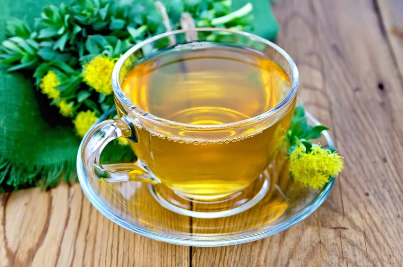 herbal-tea-in-a-cup-with-a-bouquet-of-rhodiola-rosea-on-the-boar