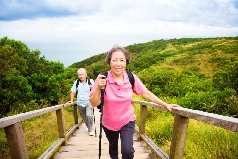 happy-senior-couple-hiking-on-the-mountain-park
