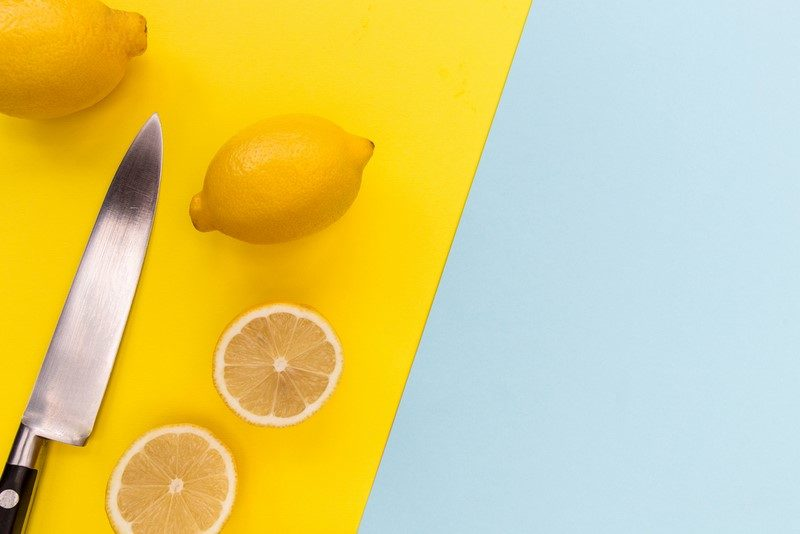 sliced-lemons-and-knife-on-bright-yellow-and-blue-background