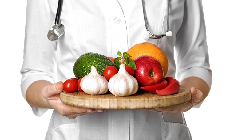 doctor-holding-wooden-board-with-heart-healthy-foods-on-white-background
