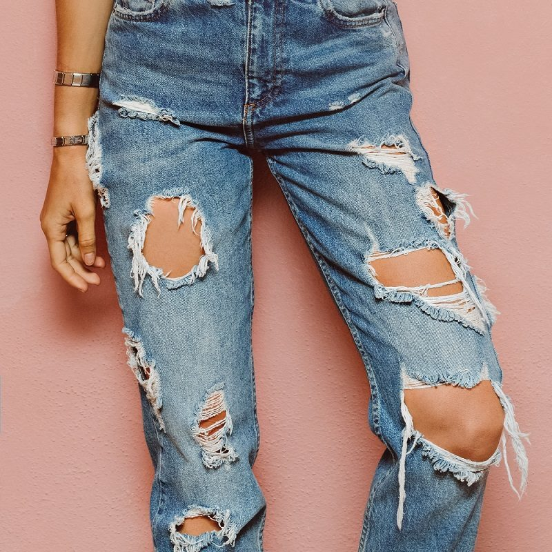 lady-in-fashionable-ripped-jeans-stands-in-pink-wall