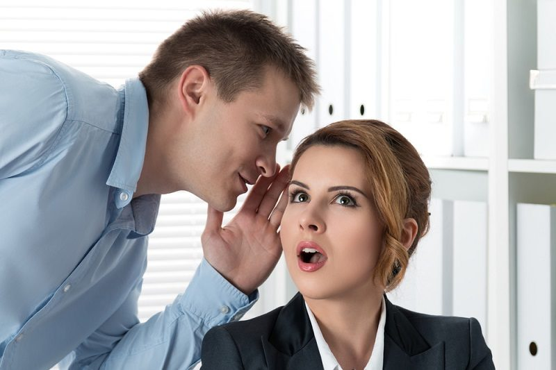 young-man-telling-gossips-to-his-woman-colleague