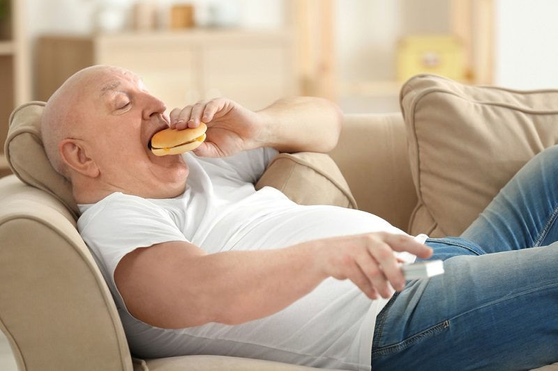 fat-senior-man-watching-tv-and-eating-hamburger-while-lying-on-sofa-at-home-sedentary-lifestyle-concept-2