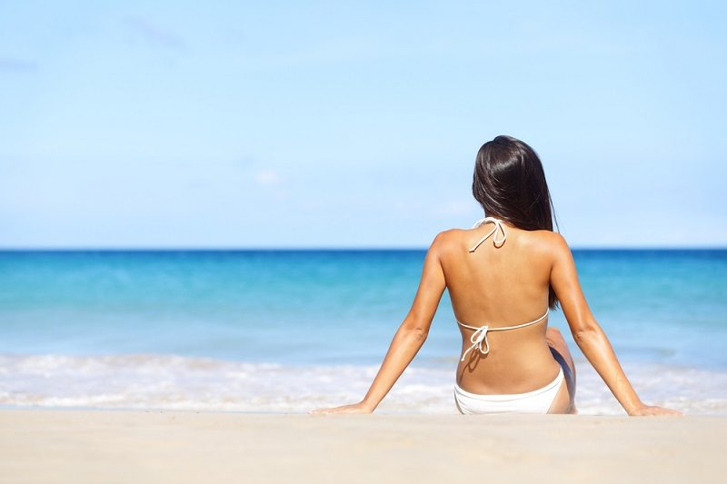woman-on-beach-sitting-in-sand-looking-at-ocean