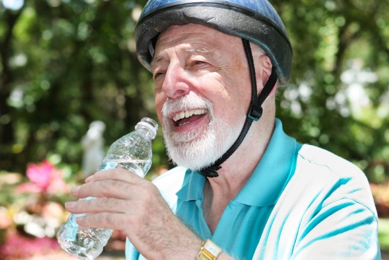 active-senior-man-wearing-a-bicycle-helmet-stops-to-drink-bottled-water