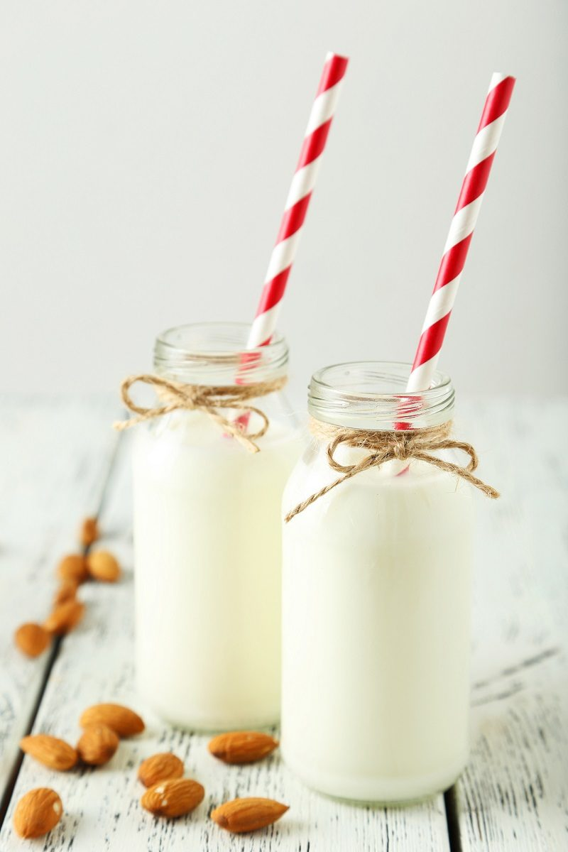 two-bottles-of-milk-with-striped-straws-and-almonds-on-white-wooden-background-2