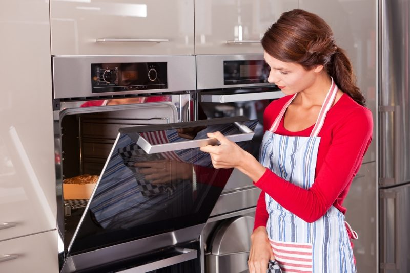 beautiful-young-woman-checking-how-her-cake-is-doing-in-the-oven