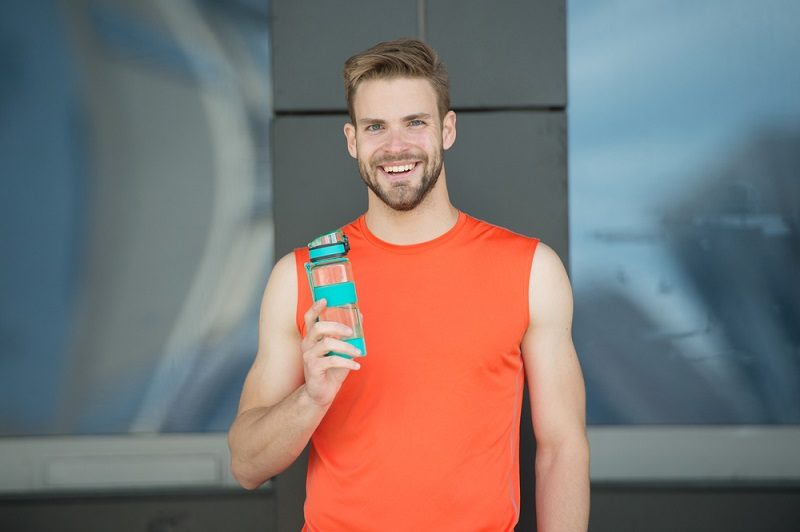 sporty-accessory-man-athlete-hold-special-sporty-bottle-care-hydration-body-after-workout-refreshing-vitamin-drink-athlete-drink-water-after-training-man-athletic-appearance-holds-water-bottle-2