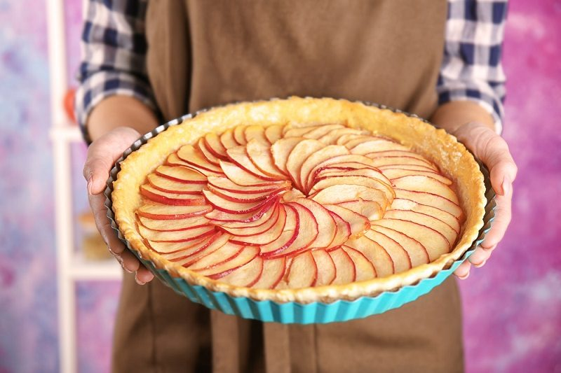 woman-holding-baking-dish-with-tasty-apple-pie