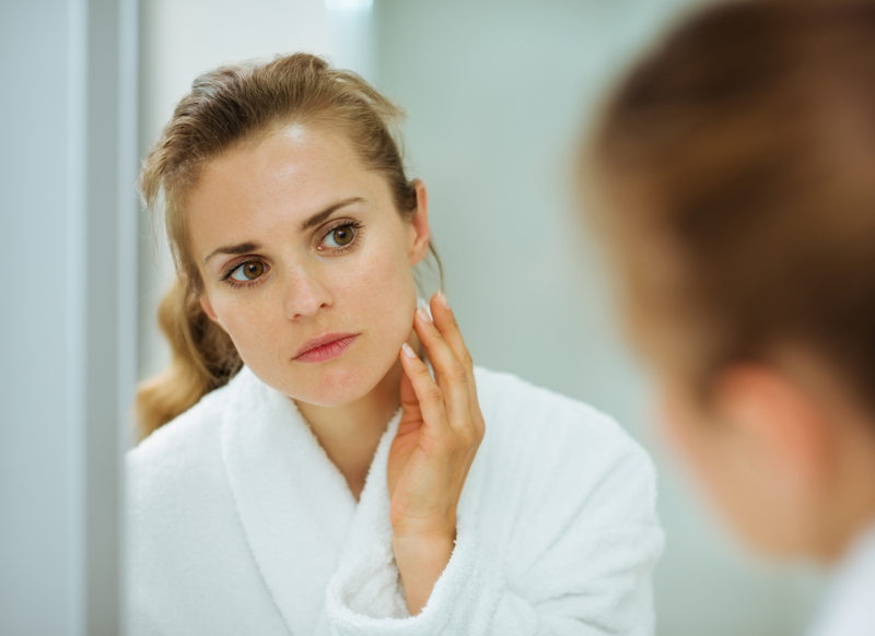 young-woman-in-bathrobe-checking-her-face-in-mirror-in-bathroom