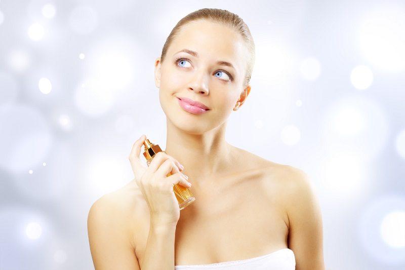 young-woman-spraying-perfume