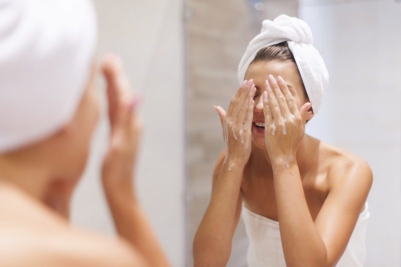 woman-washing-face-in-bathroom