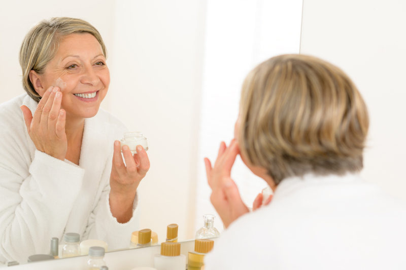 mature-woman-apply-cream-looking-bathroom-mirror