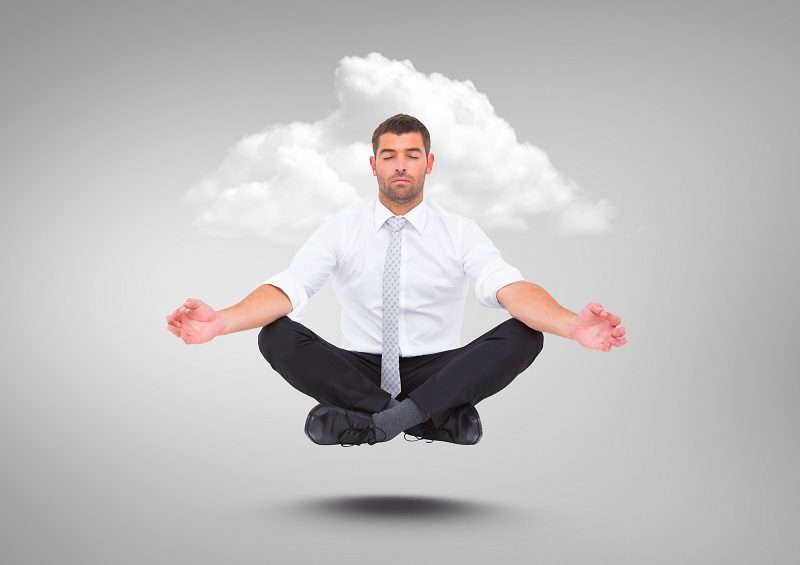businessman-meditating-floating-with-cloud-against-grey-background