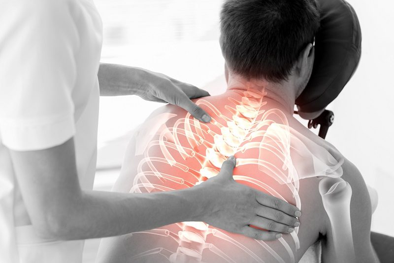 digital-composite-of-highlighted-spine-of-man-at-physiotherapy