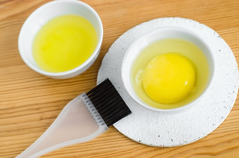 raw-egg-and-olive-oil-in-a-small-ceramic-bowls-for-prepairing-ho
