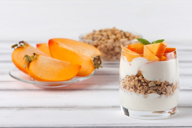 persimmon-creamy-trifle-in-beautiful-glasses-fresh-ripe-fruit-slices-on-white-wooden-background-healthy-vegetarian-food-delicious-dessert-close-up-photography-selective-focus