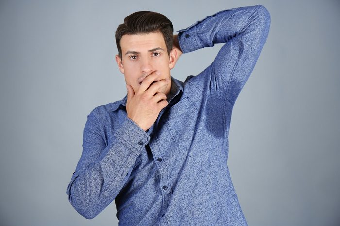 handsome-young-man-with-wet-spot-on-clothes-under-armpit-against-grey-background-concept-of-using-deodorant
