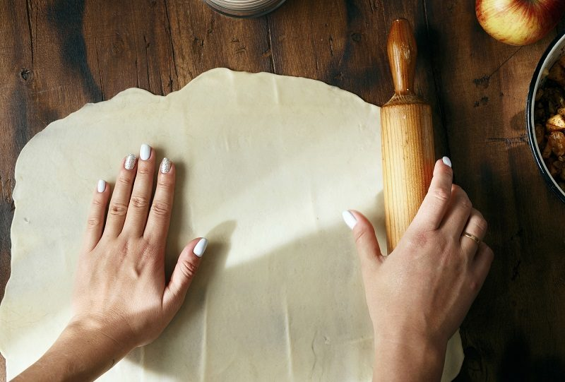 female-hands-roll-out-dough-preparation-apple-strudel-top-view