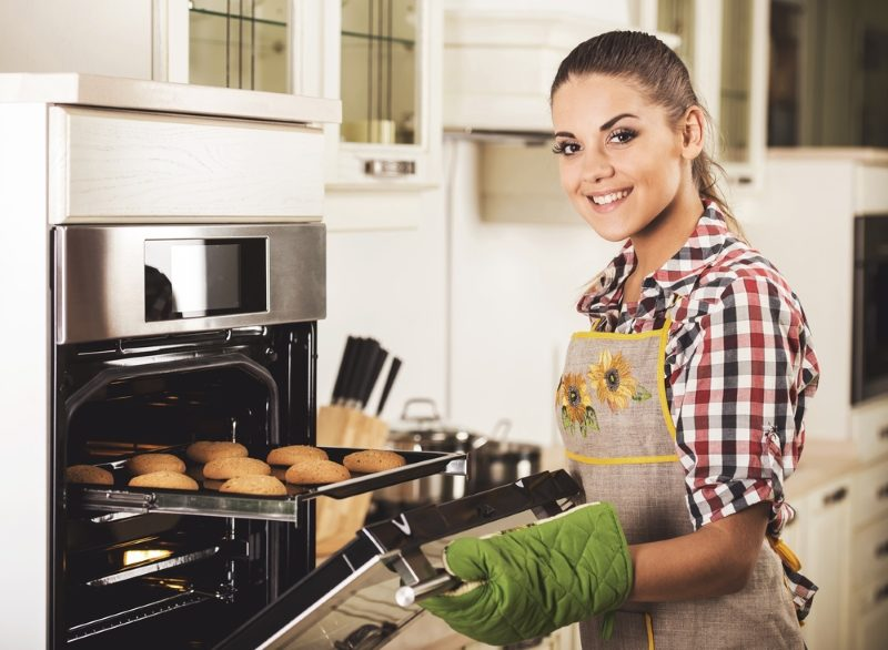 baking-fresh-cookies-in-oven-at-kitchen-young-happy-woman