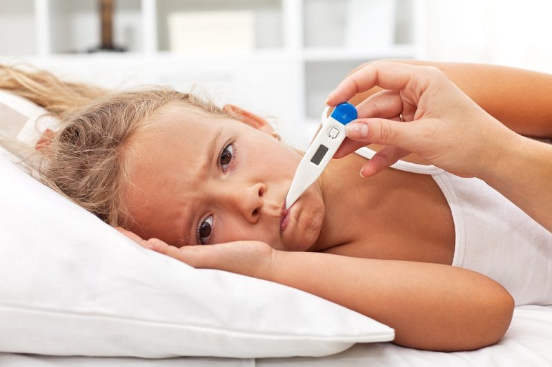 sick-little-girl-with-thermometer-laying-in-bed