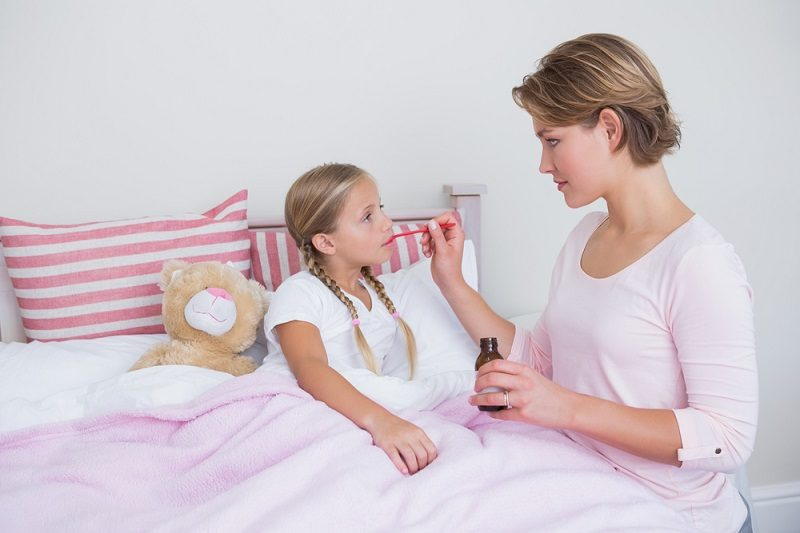 mother-about-to-give-medicine-to-sick-daughter-at-home-in-the-bedroom