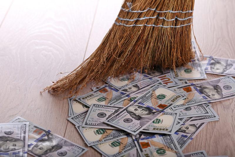dollars-and-broom-on-wooden-floor-closeup