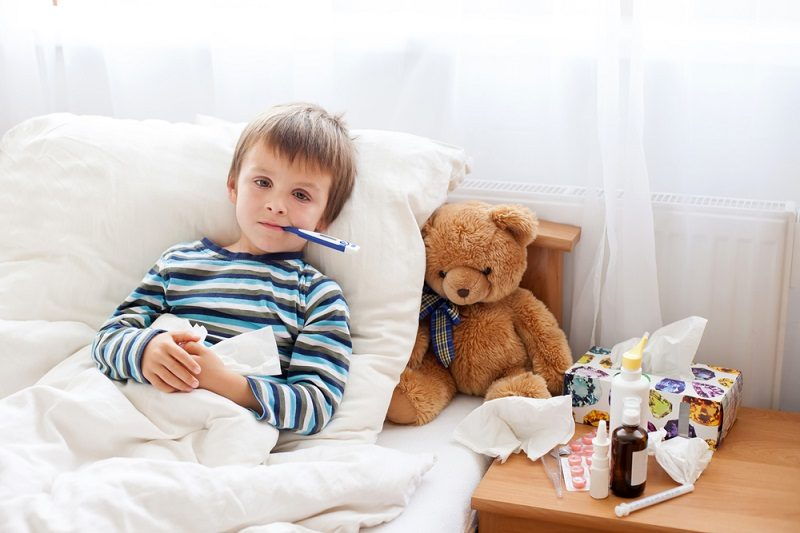 sick-child-boy-lying-in-bed-with-a-fever-resting