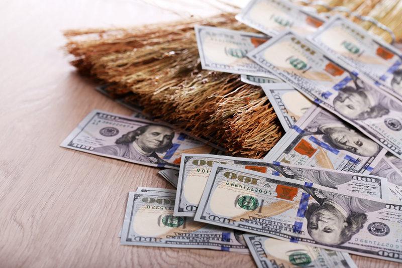 dollars-and-broom-on-wooden-floor-closeup-2