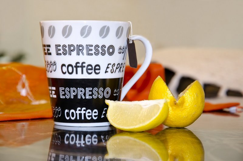 cup-of-coffee-with-lemon-slice-reflection-and-blur-background