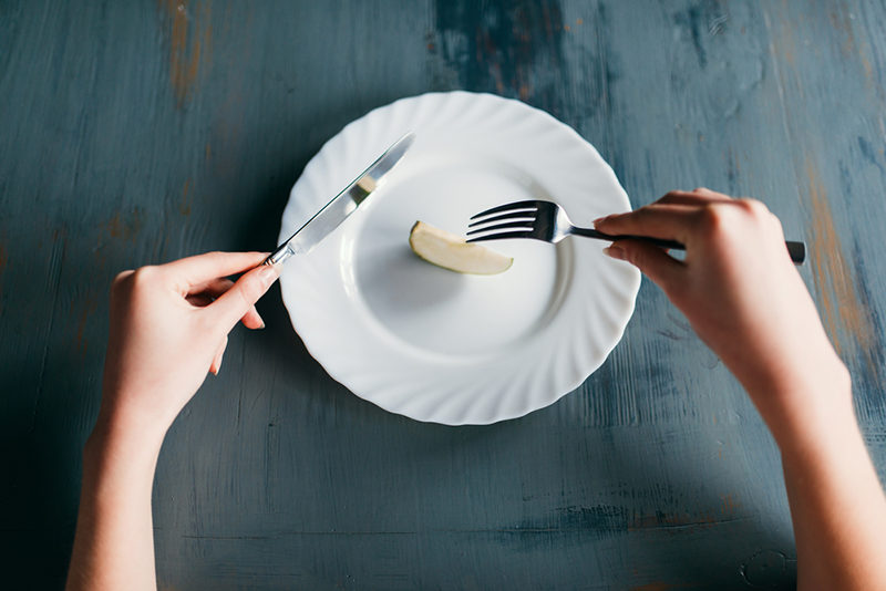 female-person-against-plate-with-a-slice-of-apple