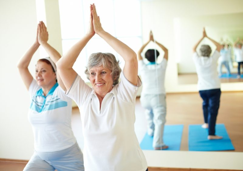 portrait-of-two-aged-females-doing-yoga-exercise-in-sport-gym