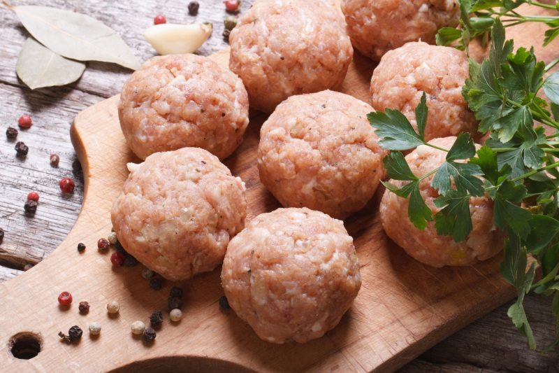 raw-meatballs-on-a-chopping-board-and-ingredients-view-from-above-macro