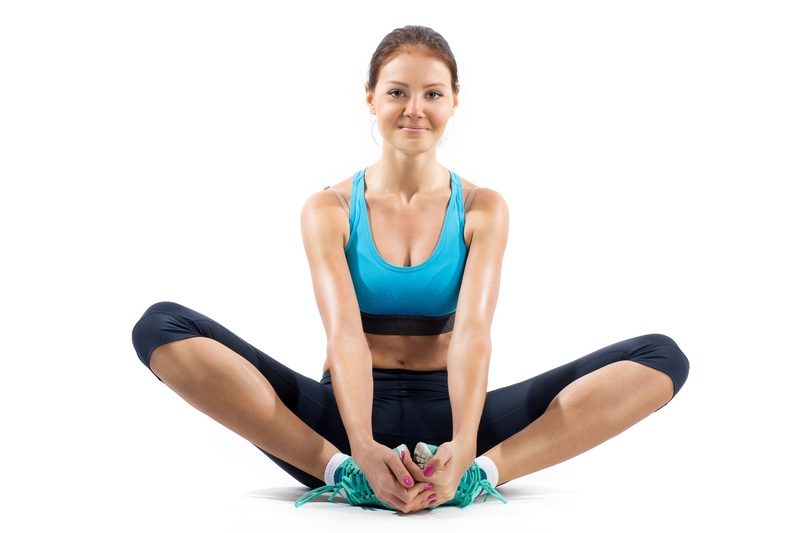 fit-woman-stretching-her-leg-to-warm-up-isolated-over-white-background